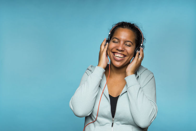 Smiling Woman Listening Music Against Blue Background