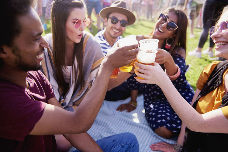 Happy Asian woman and her friends at the music festival Friends Beer Toast Festival Outdoors Party Celebratory Toast Drink Alcohol Sit Grass Celebrate Summer Music Festival Music People Group Of People Entertainment Fun Togetherness Bond Carefree Freedom Meeting Vacations Traditional Festival Youth Culture Multi Ethnic Group Traveling Carnival Popular Music Concert Live Event Pick Up Cultures Positive Emotion Smiling Happiness Asian  Indian African Adult Adults Only Women Men Happiness Joy Hold Sunlight Sunny