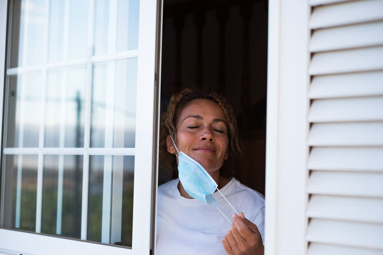 Smiling woman wearing mask at home
