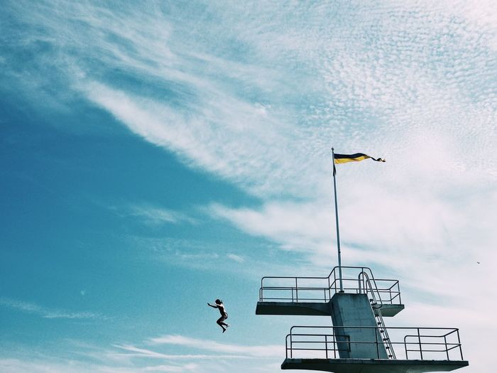 Low angle view of girl jumping from in sky