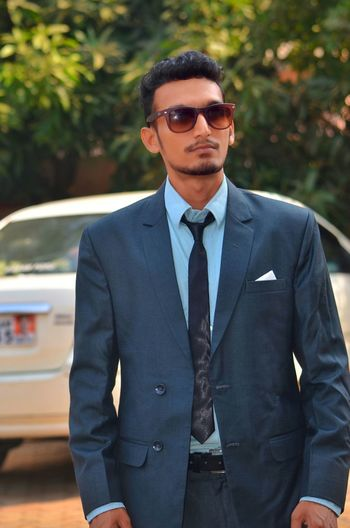Handsome businessman wearing suit while standing against car