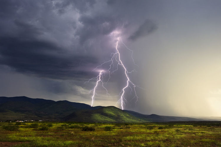 Lightning over landscape against storm clouds