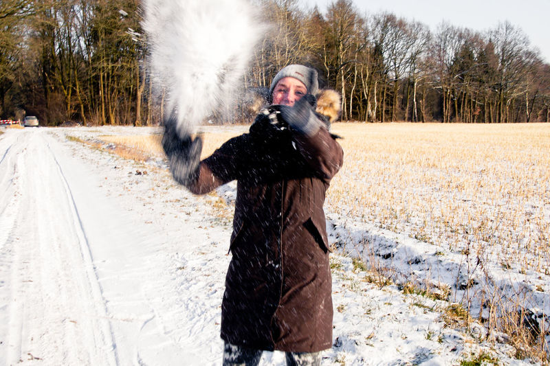 Woman Playing With Snow On Field Against Trees