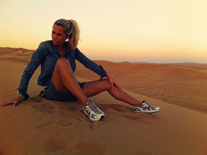 Woman sitting on sand while looking away at desert during sunset