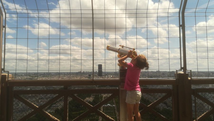 Girl looking through telescope by fence against cloudy sky