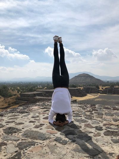 Rear View Of Woman Doing Headstand Against Sky