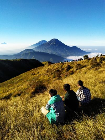 High angle view of male friends sitting on mountain against blue sky