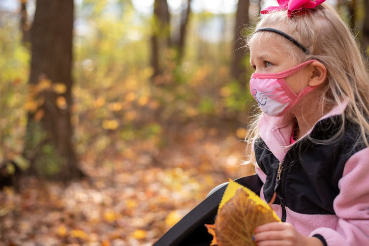 Portrait of girl wearing mask during winter