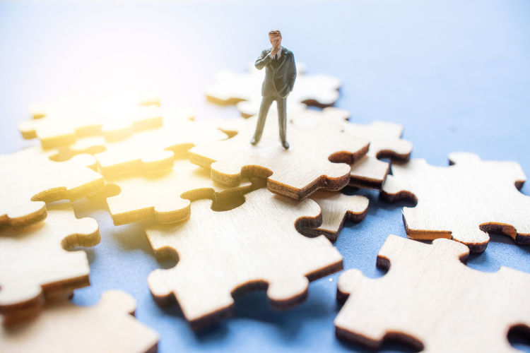 Close-Up Of Businessman Figurine On Jigsaw Piece