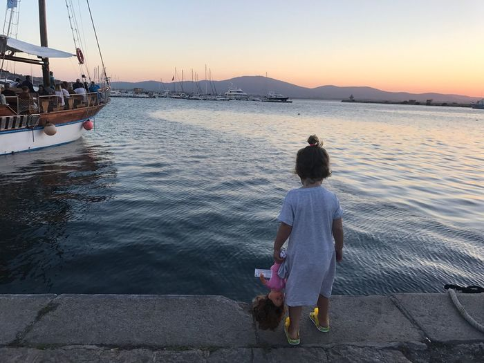 Rear view full length of girl with doll standing by sea during sunset