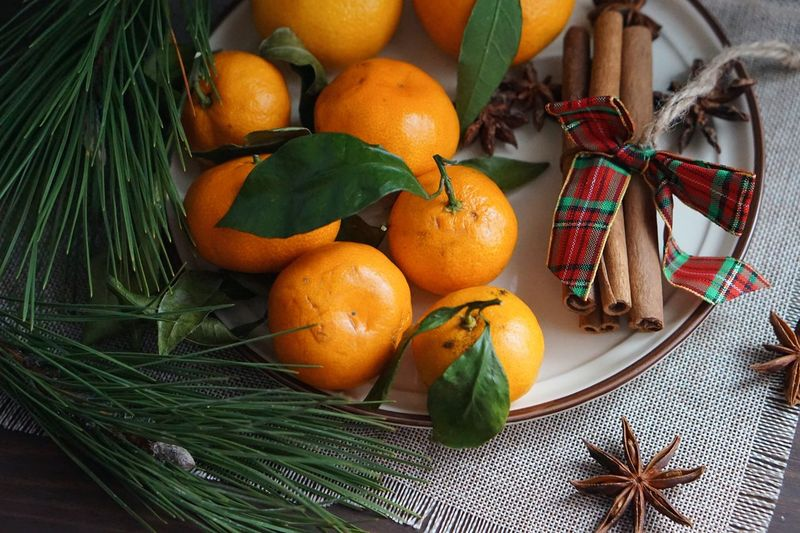 Close-up of orange fruits and cinnamon sticks on table