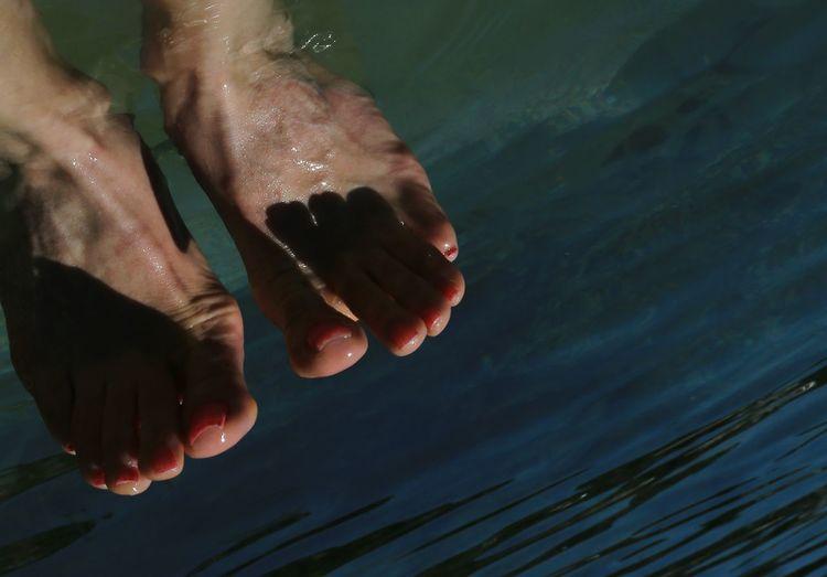 Cropped image of woman leg in river