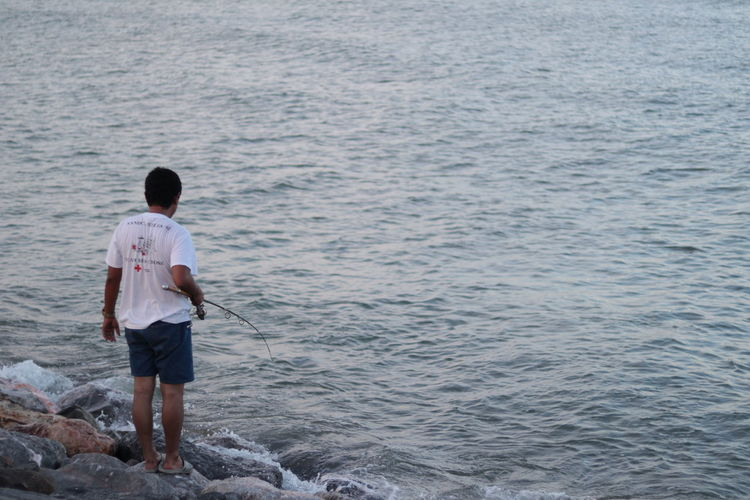 Rear view of man fishing while standing on rocks by sea