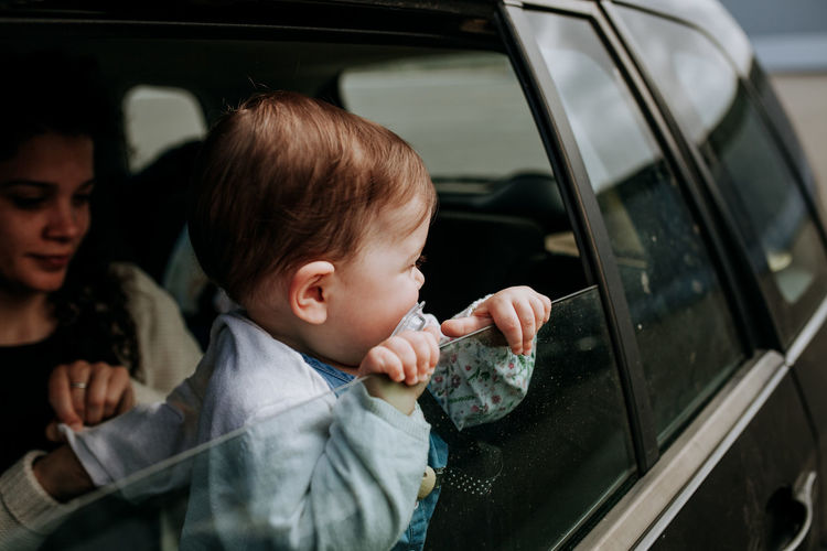 Toddler with mother looking through car window