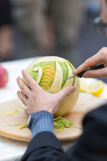 Cropped Image Of Man Carving Fruit On Table