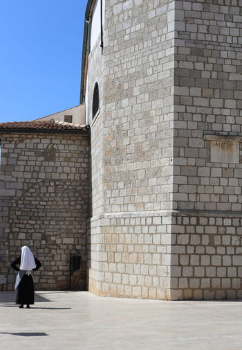 Architecture Building Exterior Built Structure Church City Contemplation Day Midday Nun One Person People Real People Solitude Stone Wall Streetphotography Sun Symmetrical Symmetry
