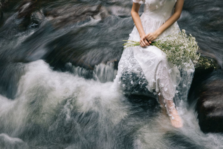 Low section of woman in wedding dress sitting on rock over river