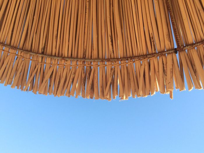 Low angle view of thatched parasol against clear blue sky