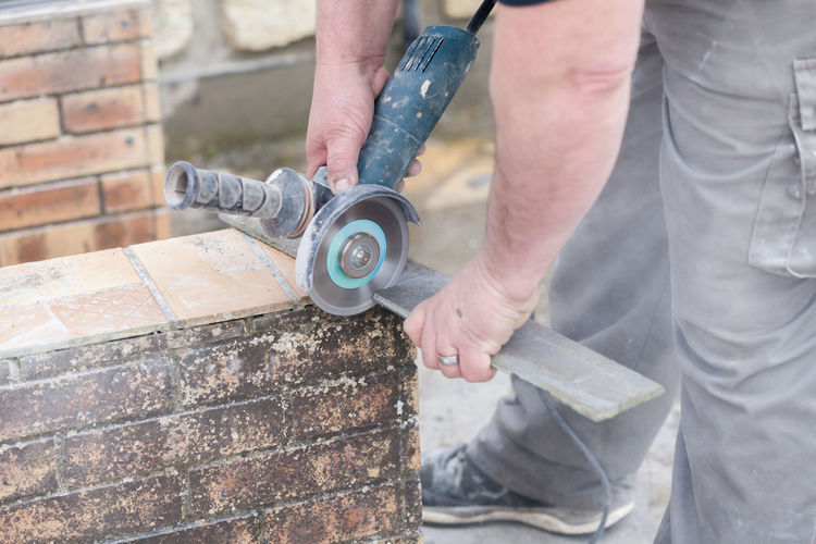 Low section of man working with grinder
