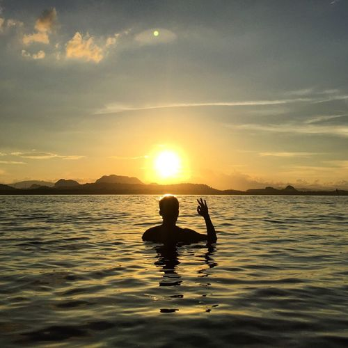 Silhouette man gesturing ok sign in sea against sky during sunset