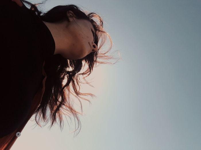 Close-up portrait of woman against sky