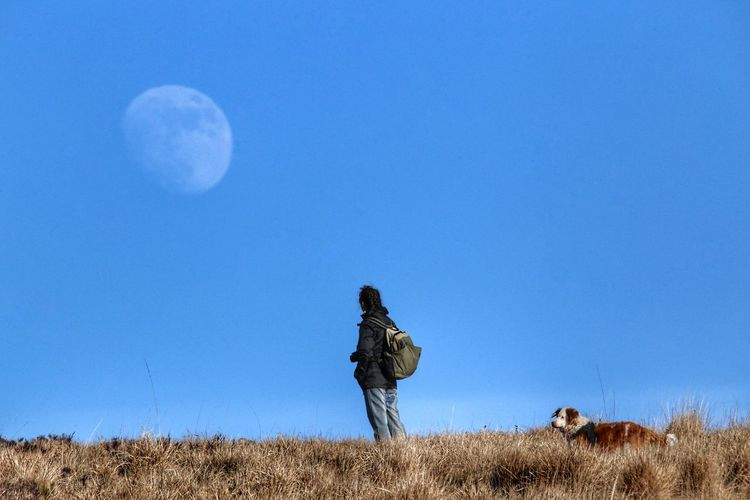 Woman with dog standing on field against sky