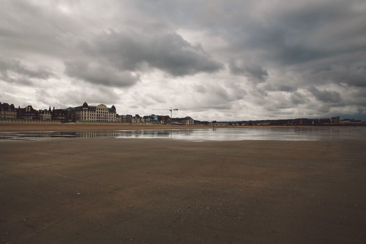 Scenic View Of Beach By Buildings Against Cloudy Sky