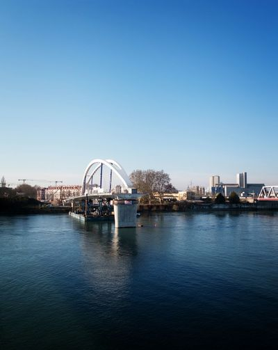 Incomplete Bridge Over River Against Clear Blue Sky