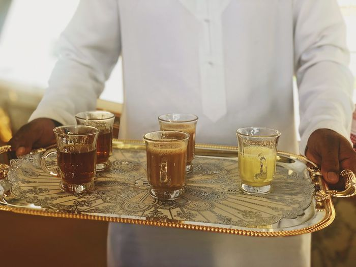 Arabic man holding a tray with drinks - traditional tea and coffee