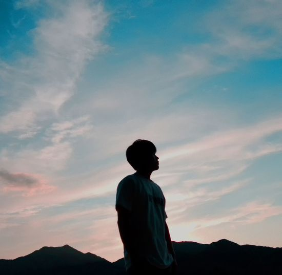 Man standing against sky and mountain during sunset