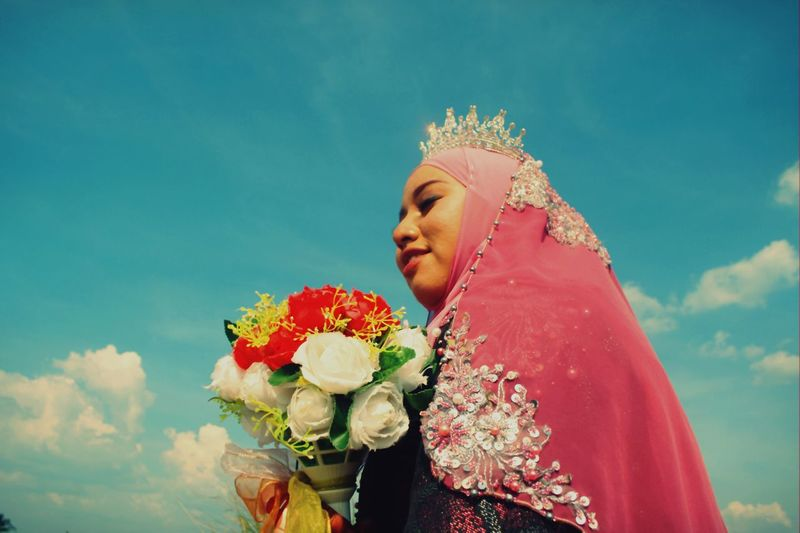 Low angle view of bride holding bouquet against sky
