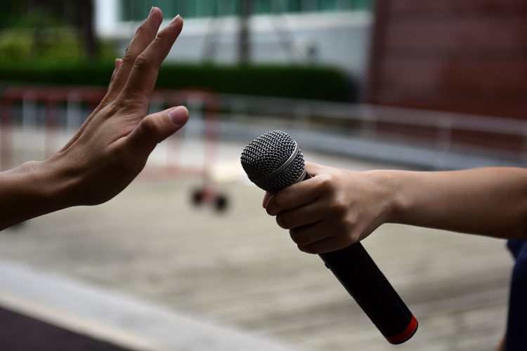 Cropped hand of woman holding microphone by man showing stop gesture