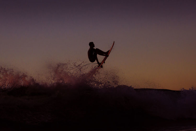 Silhouette man in mid-air against sky during sunset