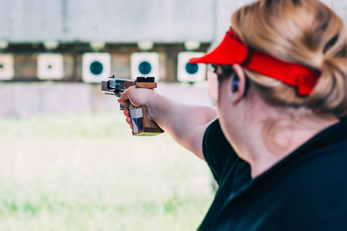 Sport Shooting Training. Woman Shooting Target Shooting Pistol Sport Shooting Gun Target Weapon Practicing Sports Training Training Female Woman Outdoor Barrel Competitive Sport Competition Protective Eyewear Handgun Concentration Technique Aiming Holding Serious Caucasian Ethnicity 30-39 Years Target Shooting