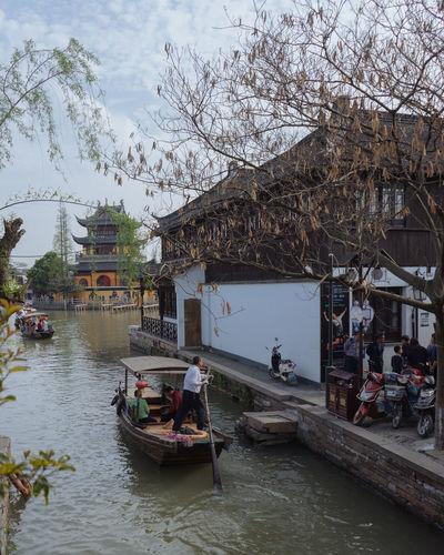 People on boat in river against buildings