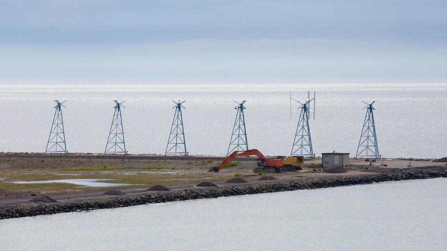 Cranes on land against sky