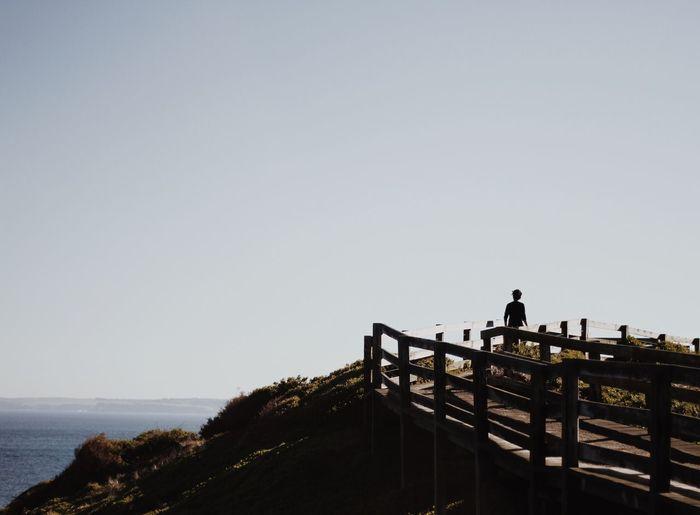 Person Walking On Boardwalk Against Sky
