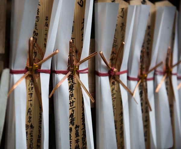 A row of wooden prayer dedications, each with delicate Japanese calligraphy and tied with a small ribbon, lines a Buddhist temple in rural Japan. Buddhism Buddhist Close-up Culture Intricate Japan Japanese  Japanese Culture No People Religion Repetition Row Tradition Traditional Wood