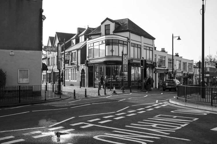 Architecture Black And White Photography Building Exterior Built Structure City Clear Sky Day Large Group Of People Monochrome Outdoors People Road Junction Sky Street Corner Street Photography Town Centre