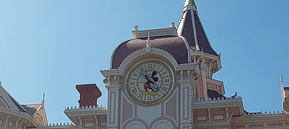 Here is a Photo shot of the Disneyland Resort Paris Park Entrance and Disney Hotel Clock Tower. This photo is located within Disneyland Resort Paris and is seen by Guests everyday when they enter the Disneyland Park. 2017 2017 Year Architecture Blue Building Exterior Built Structure City Clear Sky Clock Clock Face Clock Tower Day Disneyland Paris DLRP France France History Low Angle View Mickey Mouse Minute Hand No People Outdoors Sky Theme Parks Time Travel Destinations