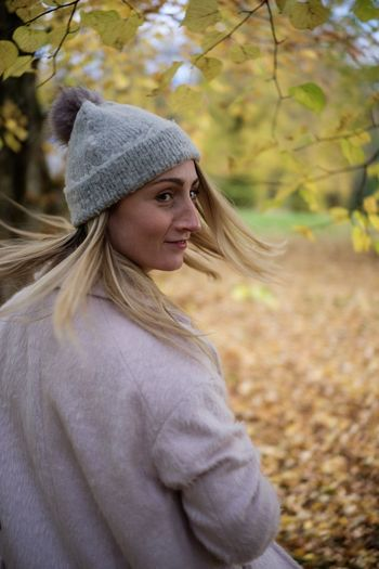 Mid adult woman in knit hat standing against autumn leaves