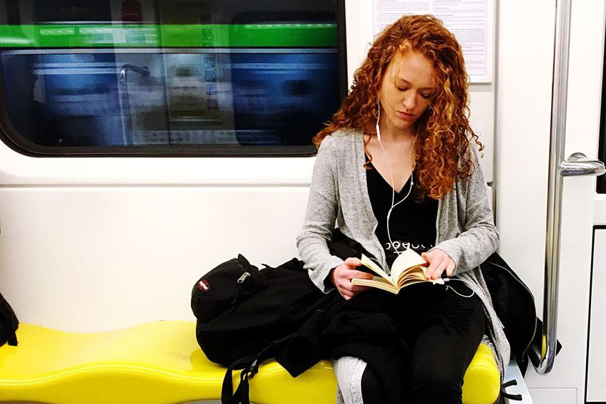 green, red and yellow. Reading One Person Real People Lifestyles Sitting Front View Leisure Activity Casual Clothing Women Young Women Hairstyle Transportation Mode Of Transportation