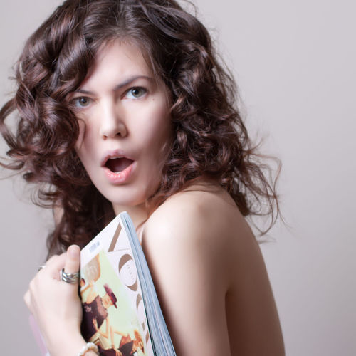 Portrait Of Shocked Young Woman With Magazine Against Gray Background