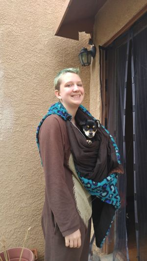 Portrait of smiling woman carrying dog in blanket while standing by house