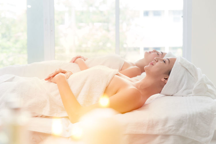 Women Wrapped In Towel While Relaxing On Massage Table In Spa