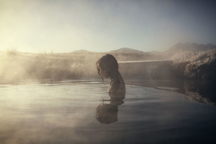 Side view of woman swimming at mammoth lake hot springs