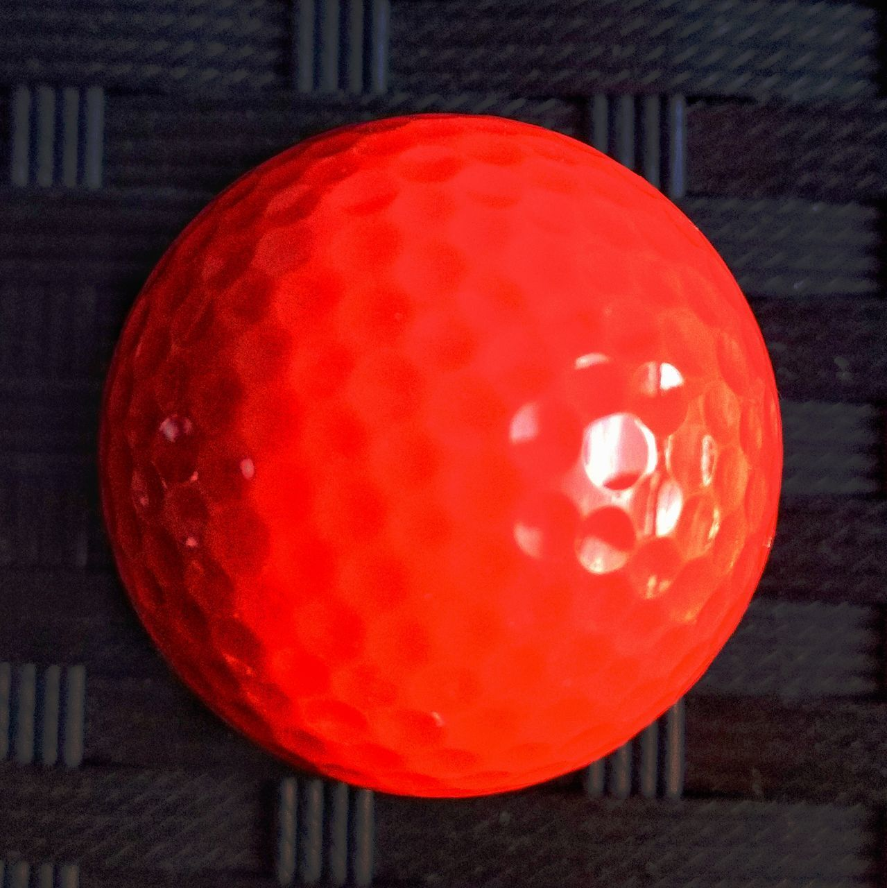 CLOSE-UP OF RED BALL ON TABLE AGAINST ILLUMINATED WALL