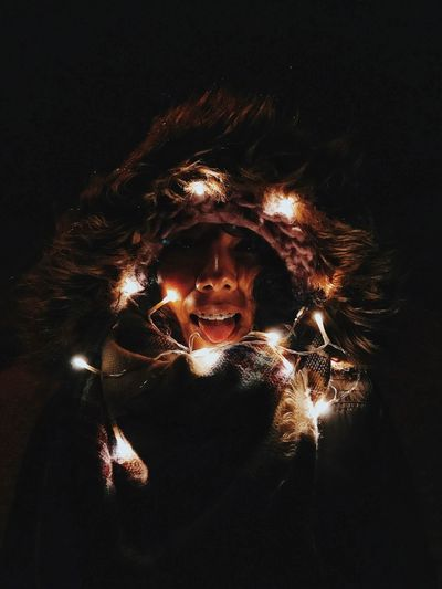 Woman wearing fur coat with illuminated string lights against black background