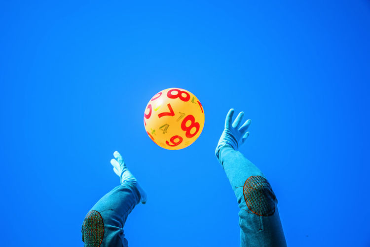 Low Angle View Of Person Catching Yellow Ball Against Blue Background