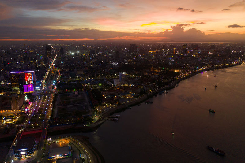 Aerial view of illuminated buildings in city at sunset